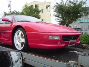 深紅に輝く積車に積まれたフェラーリ